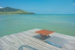 Sommer-Ferien und Feiertags-Konzept: Sommerreise am Meer, am Kissen und am Holztisch auf Terrasse im Freien für Entspannung stockfoto