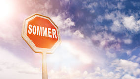 Sommer German summer on red traffic road stop sign. Sommer German for summer on red traffic road stop sign in front of blue sky with clouds and friendly sun Stock Image