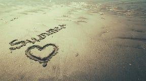 Sommer handgeschrieben im Sand des Strandes mit einem reizenden Herzen stockfotografie