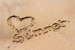 Sommer handgeschrieben im Sand des Strandes mit einem reizenden Herzen Stockbilder
