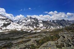 Sommer im Berg mit Schnee bewölkt sich im Himmel Stockbilder