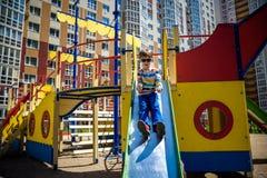 Sommer, Kindheit, Freizeit, Freundschaft und Leutekonzept - gl?cklicher kleiner Junge auf Kinderspielplatz schob vom H?gel lizenzfreie stockbilder