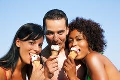 Sommer - Mann und zwei Frauen, die Eis auf Strand essen Lizenzfreie Stockfotos