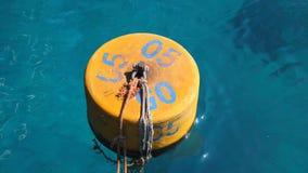 Sommer, Meer, im transparenten bläulichen Wasser schwimmt orange Boje stock footage