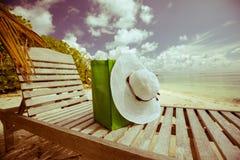 Sommer-Mode: Hut und Tasche am Aufenthaltsraum am Strand stockfotografie