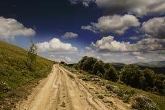 Sommer mountin Landschaft mit grünem Gras, Straße und Wolken Stockfotos