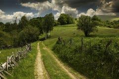 Sommer mountin Landschaft mit Landstraße, Bäumen und Wolken Lizenzfreies Stockfoto