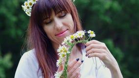 Sommer, Porträt Mitten in einem Kamillenrasen in einem Wald, spann eine junge Frau, ein Brunette einen Kranz der Kamille stock video footage