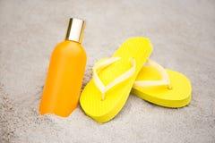 Sommer und Hautpflegekonzept - Pantoffel und Sonnenschutzmittelflasche Stockfotos