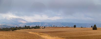 Sommeransicht des gepflogenen Feldes und Berge sind herein an einem teils bewölkten weit Lizenzfreie Stockfotos