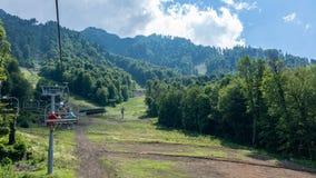 Sommeransicht vom Stuhl des Seilschleppseiles auf den grünen Steigungen der Berge lizenzfreie stockfotografie