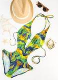 Sommerausstattung, Strandausstattung, Sommermaterial Exotischer Musterbadeanzug, hölzernes Armband, Retro- Sonnenbrille und Stroh stockfotos