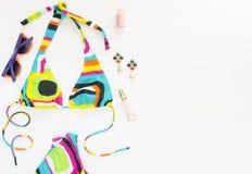Sommerausstattung, Strandausstattung, Sommermaterial Geometrischer abstrakter Musterbadeanzug, helle Sonnenbrille und Ohrringe Fl lizenzfreie stockfotos