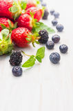 Sommerbeeren: Brombeeren, Blaubeeren, Erdbeeren auf weißem hölzernem Hintergrund Stockbild