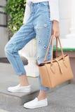 Sommerblick Weißes Hemd, Jeans, braune Ledertasche und Turnschuhschuhe Stockfoto