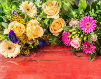 Sommerblumen: Rosen, Gänseblümchen, Lilien, Gerbera und Anemonen auf rotem hölzernem Hintergrund Stockbild