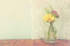 Sommerblumenstrauß von Blumen auf dem Holztisch mit tadellosem Hintergrund Weinlese gefiltertes Bild Stockfotografie