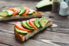 Sommerfarbsandwich mit roter Tomate und grüne Avocadoscheiben auf einem Holztisch Stockbilder