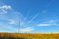 Sommerfeld mit Strompfosten- und -flugzeugbahnen im Himmel Stockfotos