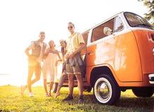 Sommerferien-, Autoreise-, Ferien-, Reise- und Leutekonzept - lächelnde junge Hippiefreunde, die Spaß über Mehrzweckfahrzeug habe lizenzfreie stockbilder