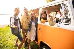 Sommerferien-, Autoreise-, Ferien-, Reise- und Leutekonzept - lächelnde junge Hippiefreunde, die Spaß über Mehrzweckfahrzeug habe stockfoto