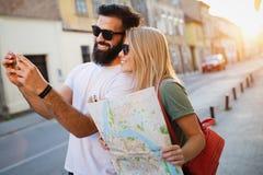 Sommerferien, Datierung und Tourismuskonzept L?chelndes gl?ckliches Paar mit Karte in der Stadt stockbilder