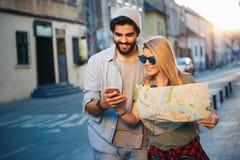 Sommerferien, Datierung und Tourismuskonzept L?chelndes gl?ckliches Paar mit Karte in der Stadt stockbild