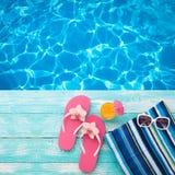Sommerferien in der Strand-Küste Mode-Accessoire-Sommer-Flipflops, Hut, Sonnenbrille auf hellem Türkis verschalen nahe dem Pool Lizenzfreies Stockfoto