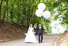 Sommerferien-, Feier- und Hochzeitskonzept - Paar mit bunten Ballonen Stockfotografie