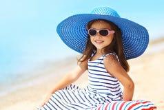 Sommerferien, Ferienkonzept - schönes kleines Mädchen des Porträts im Strohhut, gestreiftes Kleid, das auf Strand sich entspannt lizenzfreie stockbilder