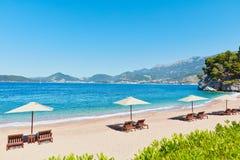 Sommerferien-Hintergrundtapete: setzen Sie Küste mit Klubsesseln unter Zelt auf dem Strand auf den Strand stockfotos