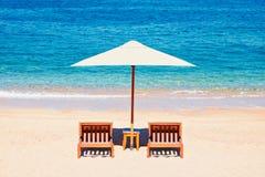 Sommerferien-Hintergrundtapete: zwei Strandklubsessel unter Zelt auf dem Strand lizenzfreie stockbilder