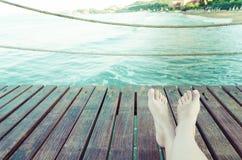 Sommerferien-Konzepthintergrund mit den Beinen über hölzernen Planken Lizenzfreies Stockbild