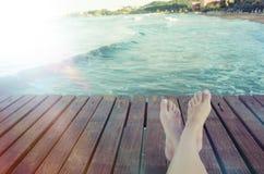Sommerferien-Konzepthintergrund mit den Beinen über hölzernen Planken Stockbild