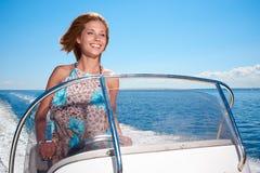 Sommerferien - Mädchen, das ein Motorboot fährt Stockfoto