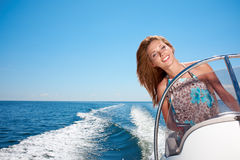 Sommerferien - Mädchen, das ein Motorboot fährt Lizenzfreies Stockfoto