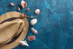 Sommerferien, Tourismus, Reise, Feiertagskonzept Seeoberteile, Strandhut und blaue Farben auf hölzernem Hintergrund Draufsicht mi Stockfoto