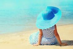 Sommerferien und Ferienkonzept - kleines Mädchen in gestreiftem Kleid, Strohhut das Sitzen auf Sandstrand genießend lizenzfreies stockbild