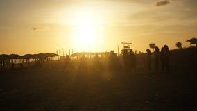 Sommerferienatmosphäre, die den Sonnenuntergang auf dem Strand genießt stockfotografie