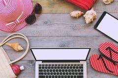 Sommerferienhintergrund mit Laptop- und Strandeinzelteilen Ansicht von oben Stockfoto