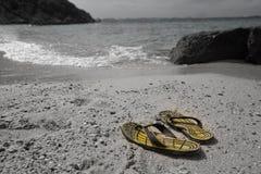 Sommerferienkonzept, gelbe gestreifte Sandalen auf Meer setzen auf den Strand stockfotos