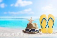 Sommerferienkonzept, Hut und Flipflop auf Sand lizenzfreie stockfotos