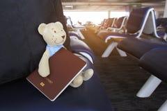 Sommerferienkonzept, Teddybär mit Pass und reisende Tasche im Flughafenabfertigungsgebäude lizenzfreie stockfotografie