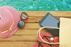 Sommerferientasche mit Tablette und Flipflops auf hölzerner Plattform Ansicht von oben Lizenzfreies Stockfoto
