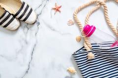 Sommerferienzusammensetzung Elegante Sandalen, gestreifte Strandtasche, Muscheln, Seestern, Wasserflasche auf Marmorhintergrund F stockbilder