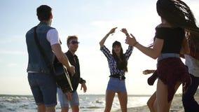 Sommerfest auf dem Strand Junge Freunde, die Cocktails, tanzend in das cirkle trinken und spielen Gitarre, Gesanglieder und stock video footage