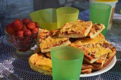 Sommerfest in der Frischluft mit Pizza, Erdbeere und Limonade Abschluss schoss oben von der Scheibe der Pizza auf der Platte stockbild