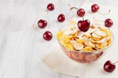 Sommerfrühstück mit goldenen Corn Flakes, reife Kirschen, Puderzucker auf weißem hölzernem Brett Lizenzfreies Stockbild