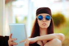 Sommerfrau tragender Bandana und Sonnenbrille mit PC Tablet Lizenzfreie Stockfotos