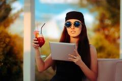 Sommerfrau tragender Bandana und Sonnenbrille mit PC Tablet Stockfotos